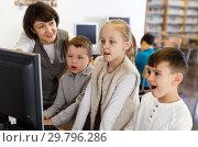 Купить «Female teacher giving lesson to kids in computer class», фото № 29796286, снято 19 декабря 2018 г. (c) Яков Филимонов / Фотобанк Лори