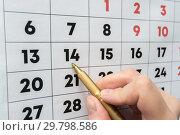 Рука маркером указывает на дату на настенном календаре. Стоковое фото, фотограф Иванов Алексей / Фотобанк Лори