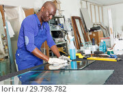 Купить «Experienced African American craftsman cleaning cut glass on table», фото № 29798782, снято 16 мая 2018 г. (c) Яков Филимонов / Фотобанк Лори