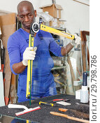 Купить «serious African American glazier using multifunction angle finder level for measuring glass size», фото № 29798786, снято 16 мая 2018 г. (c) Яков Филимонов / Фотобанк Лори
