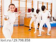 Купить «Young female fencer practicing fencing technique in training room», фото № 29798858, снято 11 июля 2018 г. (c) Яков Филимонов / Фотобанк Лори