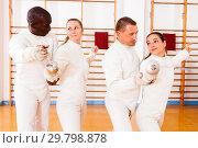 Купить «Men and women fencers posing with foils together at fencing workout», фото № 29798878, снято 11 июля 2018 г. (c) Яков Филимонов / Фотобанк Лори
