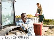 Купить «Male worker posing near tractor», фото № 29798986, снято 12 сентября 2018 г. (c) Яков Филимонов / Фотобанк Лори