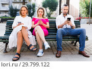 Купить «Young people are focusing on smartphones during a together walking outdoors.», фото № 29799122, снято 18 октября 2017 г. (c) Яков Филимонов / Фотобанк Лори