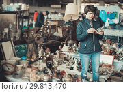 Купить «Female is visiting the market of old things and shopping outdoors.», фото № 29813470, снято 23 октября 2017 г. (c) Яков Филимонов / Фотобанк Лори