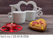Купить «Two white cups of coffee, cookies in the shape of a heart and a red candle on a wooden table on Valentine's Day», фото № 29814058, снято 2 апреля 2020 г. (c) Павел Пилипенко / Фотобанк Лори