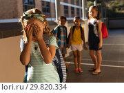 Купить «School friends bullying a crying girl in hallway of elementary school», фото № 29820334, снято 10 ноября 2018 г. (c) Wavebreak Media / Фотобанк Лори