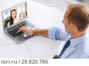 businessman having video call on laptop at office. Стоковое фото, фотограф Syda Productions / Фотобанк Лори