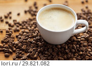 Купить «close up coffee cup and beans on wooden table», фото № 29821082, снято 7 апреля 2016 г. (c) Syda Productions / Фотобанк Лори