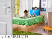 Купить «boy with tablet pc computer lying on bed at home», фото № 29821198, снято 19 апреля 2018 г. (c) Syda Productions / Фотобанк Лори
