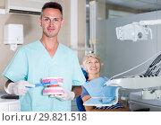 Купить «Dentist explaining tooth brushing on dental model», фото № 29821518, снято 5 июля 2017 г. (c) Яков Филимонов / Фотобанк Лори