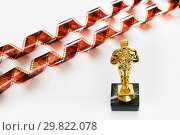 Купить «Статуэтка Оскар и кинопленка», эксклюзивное фото № 29822078, снято 28 января 2019 г. (c) Юрий Морозов / Фотобанк Лори