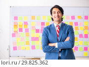 Купить «Young handsome employee with many conflicting priorities», фото № 29825362, снято 16 октября 2018 г. (c) Elnur / Фотобанк Лори