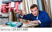 Купить «Man operating automatic screwdriver in wood workshop», фото № 29831686, снято 27 мая 2019 г. (c) Яков Филимонов / Фотобанк Лори