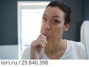 Купить «Woman brushing her teeth in bathroom», фото № 29840398, снято 3 августа 2017 г. (c) Wavebreak Media / Фотобанк Лори