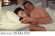 Купить «man using smartphone while girlfriend is sleeping», видеоролик № 29841070, снято 27 января 2019 г. (c) Syda Productions / Фотобанк Лори