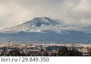 A beautiful view of the eruption of volcano Etna with smoke and snow and Catania city is in the photo in winter in Sicily (2019 год). Стоковое фото, фотограф Татьяна Куклина / Фотобанк Лори