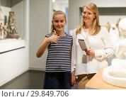 Купить «Young woman visitor with daughter with guide book looking at exhibition», фото № 29849706, снято 21 октября 2018 г. (c) Яков Филимонов / Фотобанк Лори
