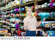 Купить «Saleswoman offering cloth in textile shop», фото № 29849834, снято 2 марта 2018 г. (c) Яков Филимонов / Фотобанк Лори
