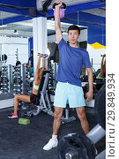 Купить «Man doing exercises with dumbbells», фото № 29849934, снято 16 июля 2018 г. (c) Яков Филимонов / Фотобанк Лори
