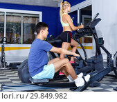 Купить «Young fitness man and woman doing cardio workout on fitness machines at gym», фото № 29849982, снято 16 июля 2018 г. (c) Яков Филимонов / Фотобанк Лори