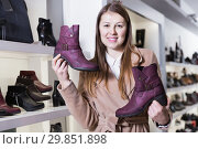 Купить «Young smiling female is demonstraiting modern ankle boots», фото № 29851898, снято 13 декабря 2017 г. (c) Яков Филимонов / Фотобанк Лори