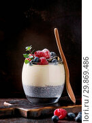 Купить «Dessert breakfast layered chia seeds pudding, rice porridge in glass decorated by fresh blueberries, raspberry, mint. Stand with wooden spoon on dark serving board over black texture background.», фото № 29869486, снято 27 мая 2020 г. (c) age Fotostock / Фотобанк Лори