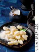 Купить «Raw uncooked potato gnocchi in black wooden plates with ingredients. Flour, grated parmesan cheese, basil, jug of cream over dark blue concrete background. Close up. Home cooking.», фото № 29871250, снято 26 мая 2020 г. (c) age Fotostock / Фотобанк Лори