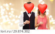 couple hiding behind red heart shaped balloons. Стоковое фото, фотограф Syda Productions / Фотобанк Лори