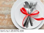 Купить «cutlery tied with red ribbon on set of plates», фото № 29874330, снято 9 февраля 2018 г. (c) Syda Productions / Фотобанк Лори