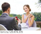 Купить «man giving woman engagement ring at restaurant», фото № 29874370, снято 9 марта 2014 г. (c) Syda Productions / Фотобанк Лори