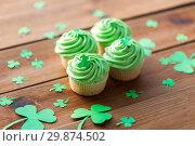 Купить «green cupcakes and shamrock on wooden table», фото № 29874502, снято 31 января 2018 г. (c) Syda Productions / Фотобанк Лори