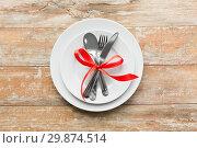 Купить «cutlery tied with red ribbon on set of plates», фото № 29874514, снято 9 февраля 2018 г. (c) Syda Productions / Фотобанк Лори