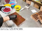 Купить «confectioner makes chocolate dessert at sweet-shop», фото № 29874586, снято 4 декабря 2018 г. (c) Syda Productions / Фотобанк Лори