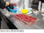 Купить «confectioner makes chocolate dessert at sweet-shop», фото № 29874662, снято 4 декабря 2018 г. (c) Syda Productions / Фотобанк Лори