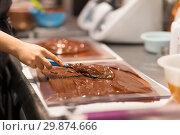 Купить «confectioner makes chocolate dessert at sweet-shop», фото № 29874666, снято 4 декабря 2018 г. (c) Syda Productions / Фотобанк Лори