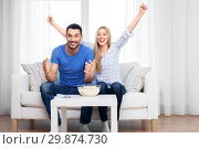 Купить «happy couple with popcorn watching tv at home», фото № 29874730, снято 9 февраля 2014 г. (c) Syda Productions / Фотобанк Лори
