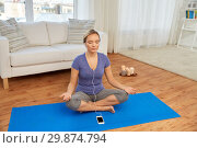 Купить «woman with music on smartphone meditating at home», фото № 29874794, снято 13 ноября 2015 г. (c) Syda Productions / Фотобанк Лори