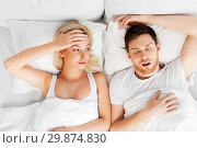 Купить «unhappy woman in bed with snoring sleeping man», фото № 29874830, снято 25 февраля 2016 г. (c) Syda Productions / Фотобанк Лори