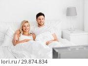 Купить «happy couple lying in bed at home and watching tv», фото № 29874834, снято 25 февраля 2016 г. (c) Syda Productions / Фотобанк Лори