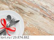 Купить «cutlery tied with red ribbon on set of plates», фото № 29874882, снято 9 февраля 2018 г. (c) Syda Productions / Фотобанк Лори