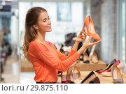 Купить «happy young woman choosing shoes at store», фото № 29875110, снято 22 сентября 2017 г. (c) Syda Productions / Фотобанк Лори