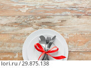 Купить «cutlery tied with red ribbon on set of plates», фото № 29875138, снято 9 февраля 2018 г. (c) Syda Productions / Фотобанк Лори