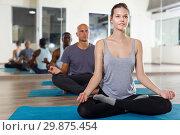 Young female meditating in yoga position Padmasana during group training. Стоковое фото, фотограф Яков Филимонов / Фотобанк Лори