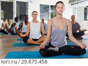 Купить «Nice girl making yoga meditation in lotus pose», фото № 29875458, снято 30 июля 2018 г. (c) Яков Филимонов / Фотобанк Лори