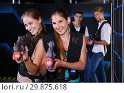 Купить «Two sporting women with laser pistols», фото № 29875618, снято 27 августа 2018 г. (c) Яков Филимонов / Фотобанк Лори
