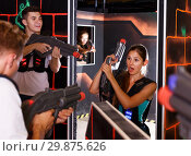Купить «Excited people playing enthusiastically laser tag game», фото № 29875626, снято 27 августа 2018 г. (c) Яков Филимонов / Фотобанк Лори