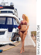 Купить «Beautiful sexy girl with a slim figure is standing on a wooden pier in a yacht club», фото № 29876154, снято 27 июня 2017 г. (c) katalinks / Фотобанк Лори