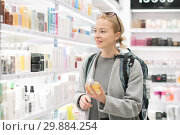 Купить «Blond young female traveler wearing travel backpack choosing perfume in airport duty free store.», фото № 29884254, снято 10 января 2019 г. (c) Matej Kastelic / Фотобанк Лори