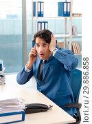 Купить «Young handsome male employee with too much work in the office», фото № 29886858, снято 10 ноября 2018 г. (c) Elnur / Фотобанк Лори